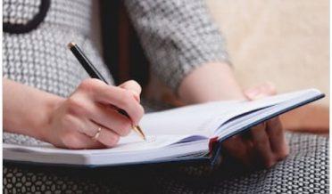 لڑکی قلم کے ساتھ کاپی پر لکھ رہی ہے