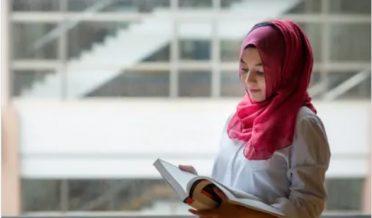 باحجاب مسلمان طالبہ کتاب کا مطالعہ کرتے ہوئے