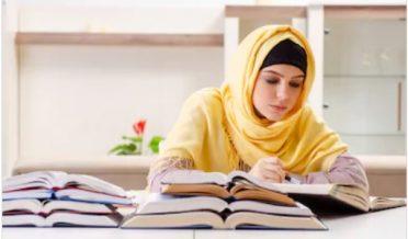 سکارف اوڑھے ہوئے مسلمان خاتون کتابیں پڑھتے ہوئے