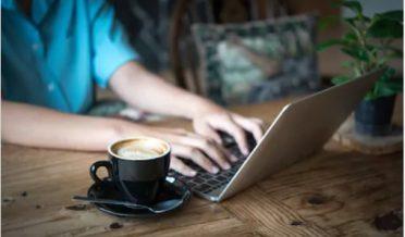 لیپ ٹاپ پر کام کرتے ہوئے لڑکی اور کافی کا کپ