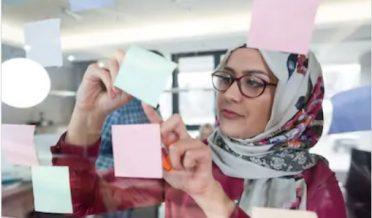 باحجاب لڑکی دفتر میں سٹکی نوٹس لگاتے ہوئے