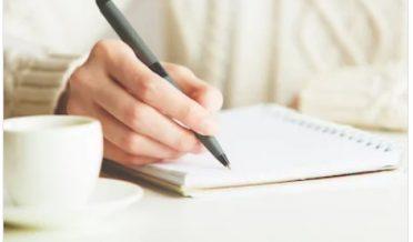 خاتون قلم کے ساتھ نوٹ بک پر لکھتے ہوئے