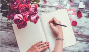 خاتون نوٹ بک پر لکھتے ہوئے اور پھولوں کا گل دستہ