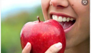 لڑکی سرخ سیب کھاتے ہوئے